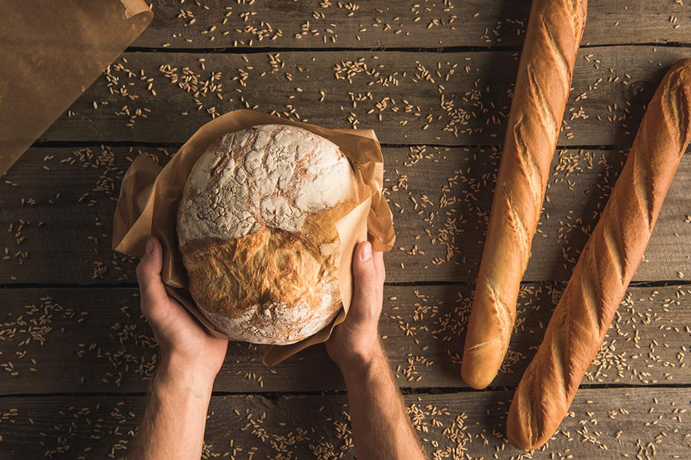 hands holding a loaf of fresh baked bread